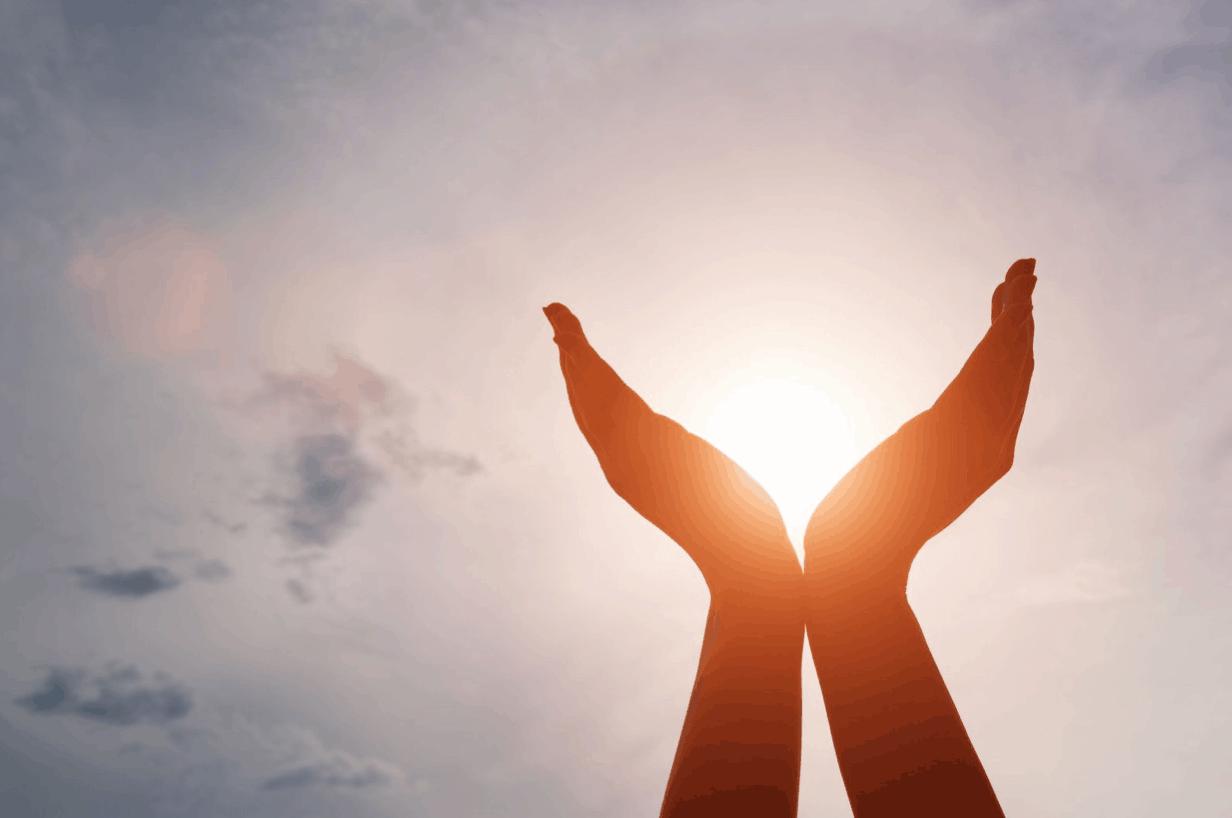 Hände, die im Gegenlicht die Sonne einfangen