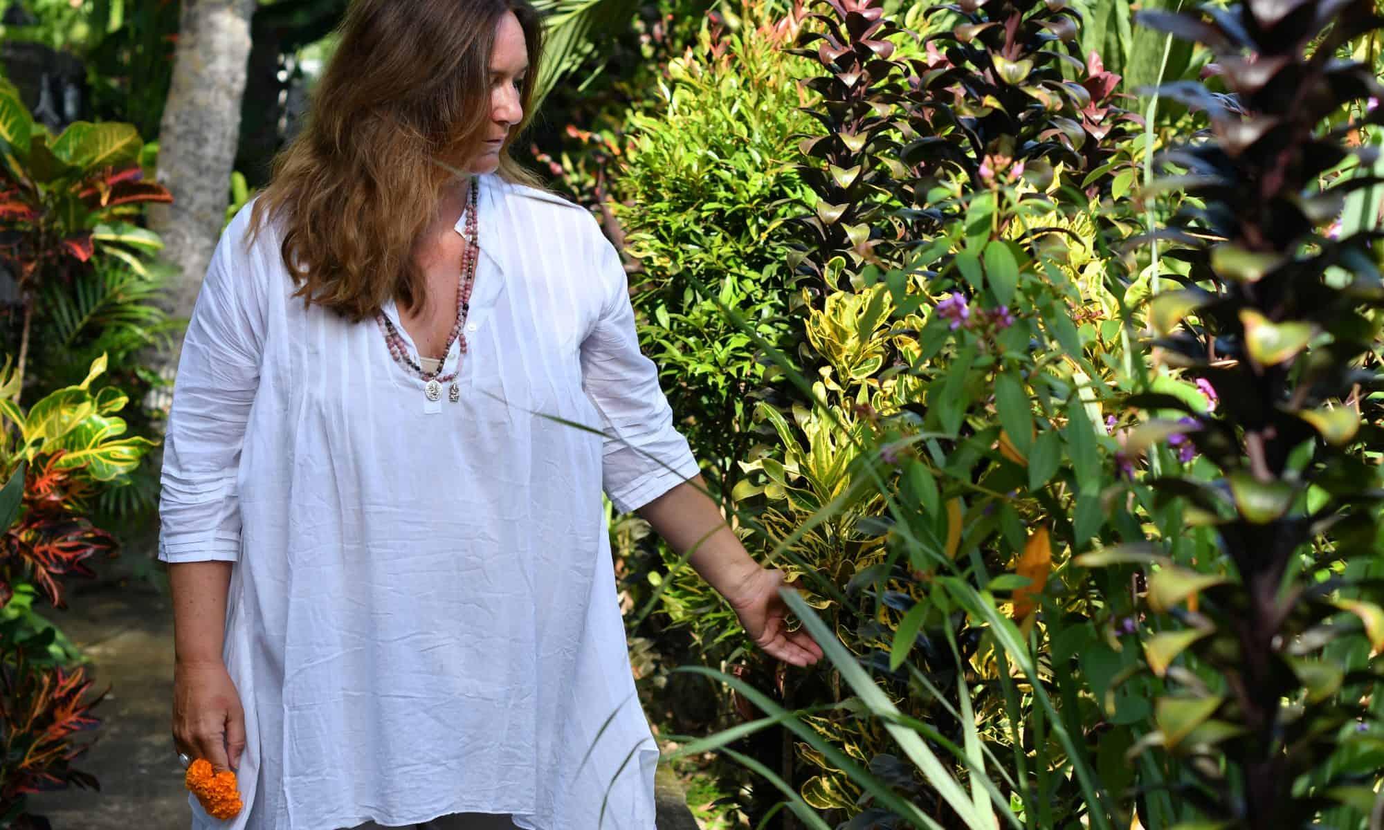 Mia in Bali eine Pflanze berührend