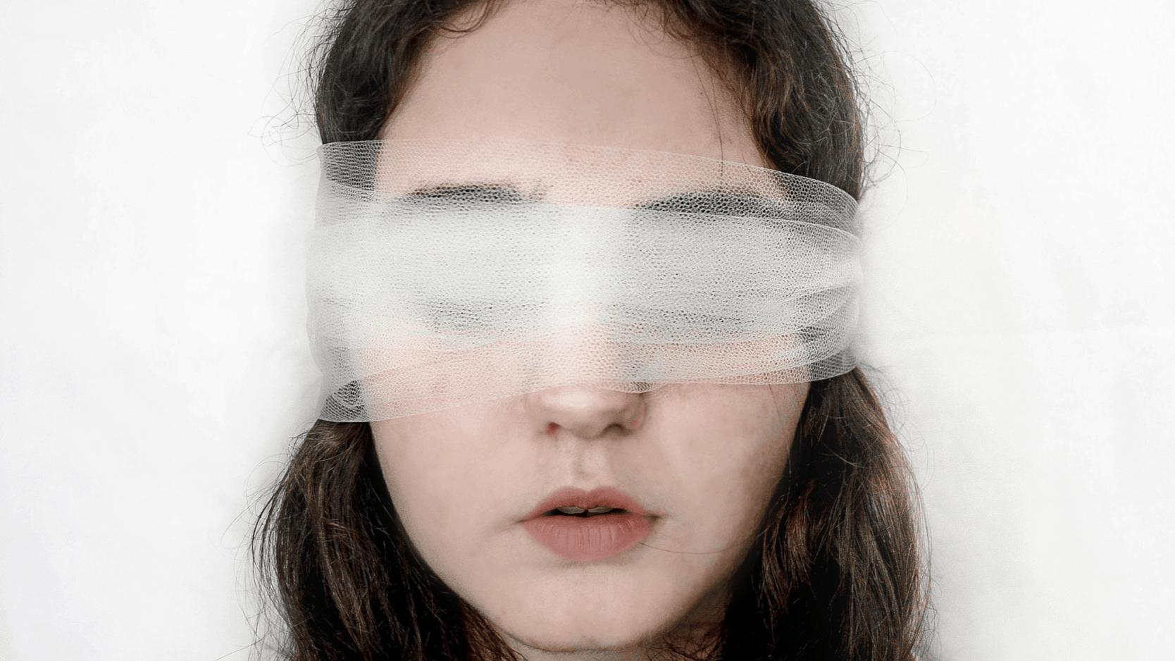 Dunkelhaarige Frau, die ihre Augen mit einem Sc heller verbunden hat