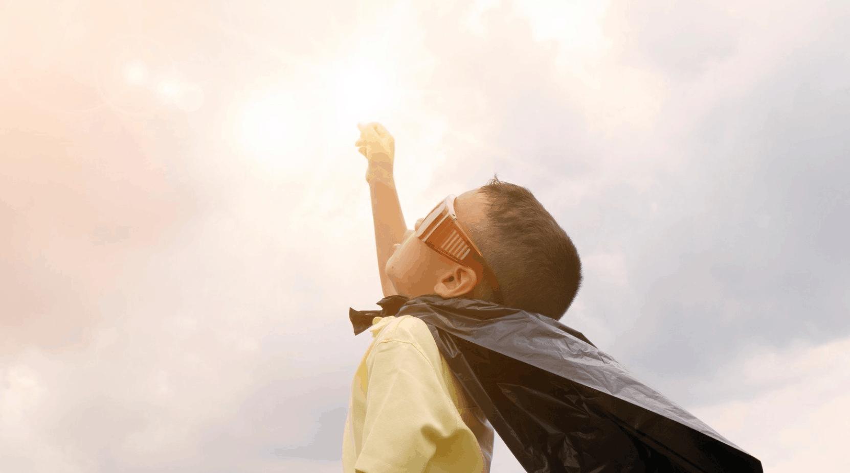 ein kleiner Junge mit Heldenumhang streckt die rechte Hand nach oben